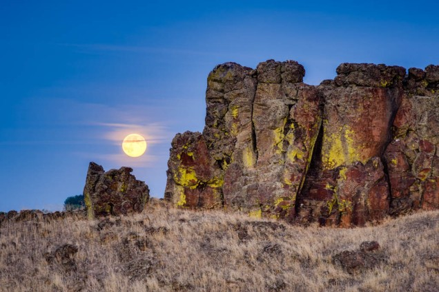 The Harvest Full Moon rising over rock formations in Grant County, Washington on a late September Summer evening.